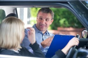 DVSA driver's record. A driving instructor sitting in a learner car with a student going through the DVSA driver's record. The record is clipped to a blue clip board. He is smiling while discussing this with his student.